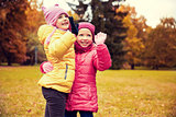 happy little girls waving hands in autumn park