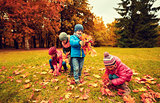 group of children collecting leaves in autumn park