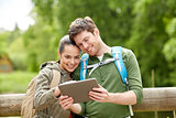 happy couple with backpacks and tablet pc outdoors