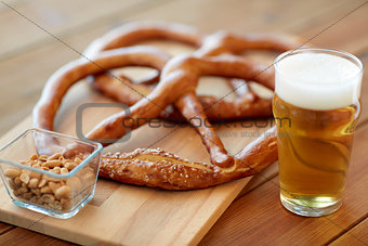 close up of beer, pretzels and peanuts on table