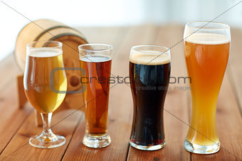 close up of different beers in glasses on table