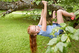 happy little girl hanging on tree in summer park