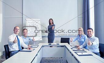 group of smiling businesspeople showing thumbs up