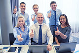 business people showing thumbs up in office