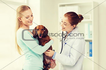 happy woman with dog and doctor at vet clinic