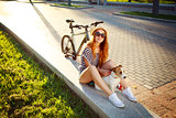Smiling Hipster Girl with Pet and Bike in Summer
