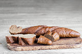 Whole and sliced bread on a gray wooden background