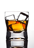 Glasss of whiskey with ice cubes with reflection