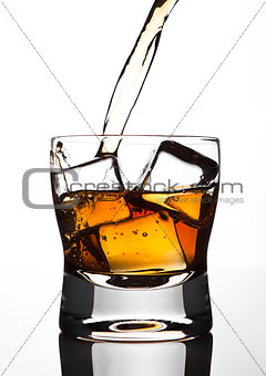 Pouring whiskey to the glass with ice cubes
