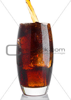 Pouring cola soda drink into the glass with ice