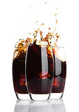 Glasses of cola with splash and ice cubes on white