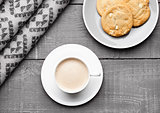 Cup of cappuccino with grey wool scarf and cookies