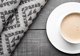 Cup of cappuccino with grey wool scarf on wood