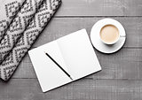 Cup of cappuccino with grey wool scarf and diary