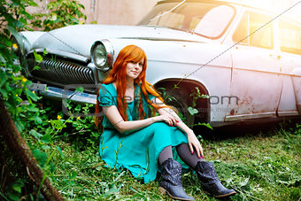 Bright young woman posing near old car