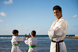 Happy Karate Sport Instructor Watching Young Boys Fighting
