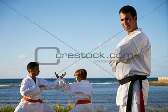 Portrait Of Confident Karate Trainer Watching Children Fight