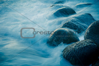 Waves swelling over rocks on the shore.