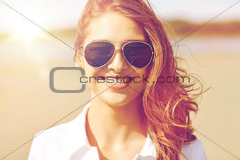 smiling young woman in sunglasses on beach
