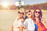 group of smiling women taking selfie on beach