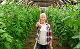 happy senior woman at farm greenhouse