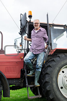 old man or farmer getting out of tractor at farm