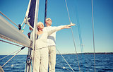 senior couple enjoying freedom on sail boat in sea