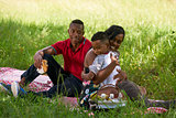 African American Family With Father Mother Child Hugging In Park