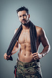 Cool athletic man posing with towel