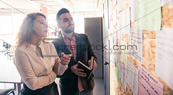 Businessman and businesswoman communicating in office