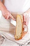 Baker cutting fresh made bread.