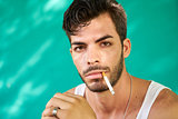 Portrait Of Young Hispanic Man Smoking Cigarette