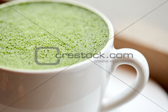 close up of cup with matcha green tea latte