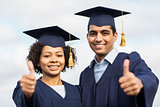 happy students or bachelors showing thumbs up