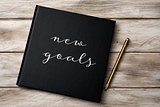 text new goals in a notebook