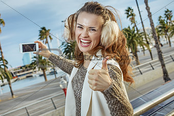 tourist woman showing thumbs up and taking photo with smartphone