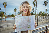 smiling modern woman on embankment in Barcelona, Spain with map
