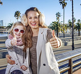 mother and child tourists in Barcelona, Spain showing thumbs up