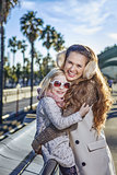mother and daughter tourists on embankment in Barcelona hugging