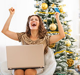 Happy young woman with credit card and laptop rejoicing