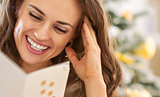 Smiling young woman reading christmas postcard