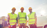 happy male builders in high visible vests outdoors