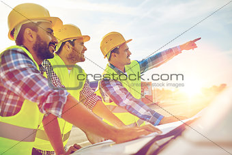 close up of builders with blueprint on car hood