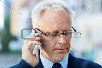 close up of old businessman calling on smartphone