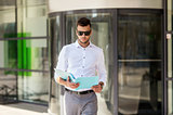 young man with business file on city street