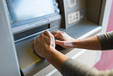 close up of hand entering pin code at atm machine