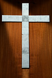 White Marble Cross on a Wooden Background