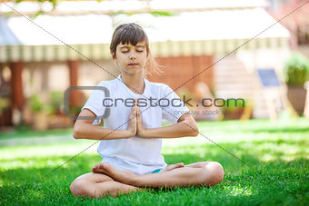 Little girl meditating while sitting in lotus position on grass
