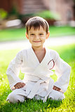 Smiling little boy in kimono sitting on grass in park