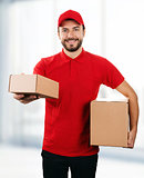 delivery service - young smiling deliveryman with cardboard boxe